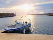 Barco de pesca en el agua de la calma de la puesta del sol Una motora para la pesca deportiva atada a un embarcadero de madera Imagenes de archivo