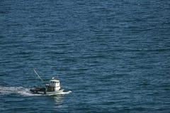 Barco de pesca en el océano azul Fotos de archivo