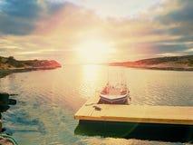 Barco de pesca en el puerto de la bahía, agua tranquila de la puesta del sol Una motora para la pesca deportiva Imagenes de archivo