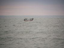 Barco de pesca en la distancia en el Océano Atlántico imagen de archivo