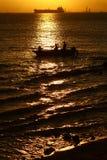 Barco de pesca en la puesta del sol Imagenes de archivo