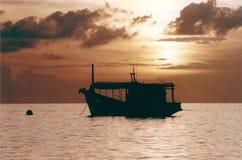 Barco de pesca en la puesta del sol fotos de archivo