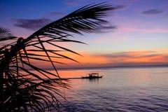 Barco de pesca en la puesta del sol foto de archivo