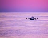 Barco de pesca en medio de Violet Skies en el golfo Fotos de archivo