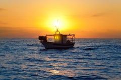Barco de pesca en salida del sol en el mar Mediterráneo Foto de archivo