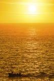 Barco de pesca en un océano de oro imagenes de archivo