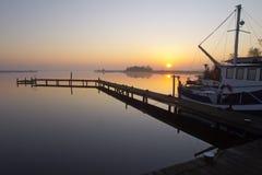 Barco de pesca a lo largo de un embarcadero Foto de archivo libre de regalías