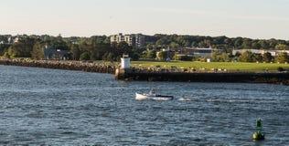Barco de pesca más allá de Maine Lighthouse Imagenes de archivo