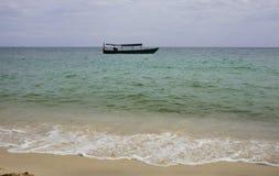 barco de pesca de madeira nas águas azuis e verdes de Camboja fotografia de stock