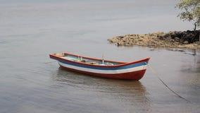 Barco de pesca de madera coloreado vacío anclado de la costa almacen de video
