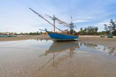 Barco de pesca de madera en la playa de la marea baja fotos de archivo
