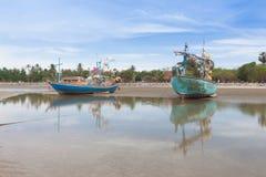 Barco de pesca de madera en la playa de la marea baja fotos de archivo libres de regalías