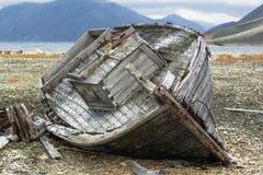Barco de pesca de madera en una orilla rocosa Imagenes de archivo