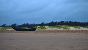 barco de pesca de madera solitario en la playa del mar con los árboles de la arena de una playa y de pino imagen de archivo libre de regalías