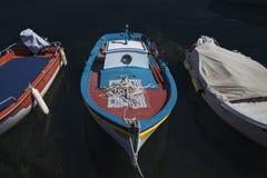 Barco de pesca mediterrâneo vermelho, branco, amarelo e azul ensolarado na água em Euboea - Nea Artaki, Grécia Fotos de Stock Royalty Free
