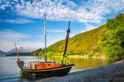 Barco de pesca na costa do lago Wakatipuat Wilson Ba Fotos de Stock Royalty Free