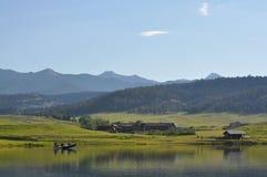 Barco de pesca na lagoa nas montanhas imagens de stock