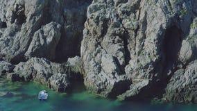 Barco de pesca na lagoa de turquesa com as rochas enormes em Grécia filme