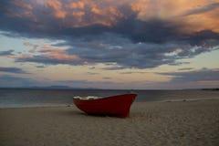 Barco de pesca na praia da areia após o por do sol Barco na costa de mar no céu nebuloso da noite Férias de verão no mar Pesca e Imagem de Stock Royalty Free