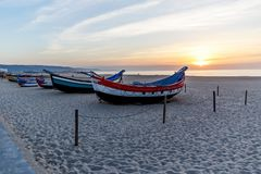 Barco de pesca na praia no por do sol imagens de stock