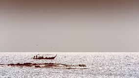 Barco de pesca nativo da silhueta em cores do sepia fotos de stock royalty free