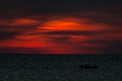 Barco de pesca no mar no por do sol Fotografia de Stock