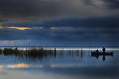 Barco de pesca que cruza o lago foto de stock