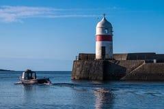 Barco de pesca que dirige hacia fuera al mar más allá del puerto y del faro fotos de archivo libres de regalías