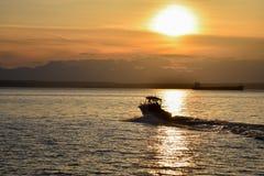 Barco de pesca que dirige para fora no por do sol Fotografia de Stock Royalty Free