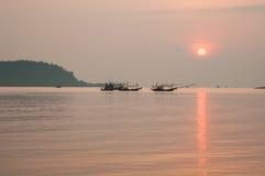 Barco de pesca que flota en el mar en la salida del sol Foto de archivo
