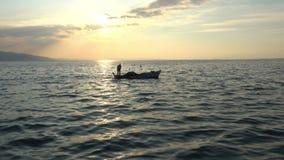 Barco de pesca que flota en la puesta del sol de oro y los rayos amarillos del sol almacen de video
