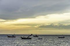 Barco de pesca que flutua no mar com céu do por do sol Fotografia de Stock