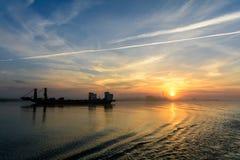 Barco de pesca que sale del puerto en un fondo de niebla horizont Imagenes de archivo
