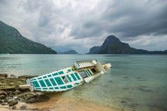 Barco de pesca quebrado encalhado após o tufão no tempo chuvoso no EL Nido, Palawan, Filipinas fotografia de stock