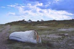 barco de pesca revolvido na costa próxima da charneca fotografia de stock