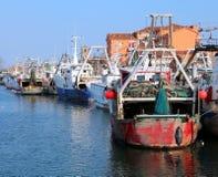 Barco de pesca rojo en el canal con muchos otros barcos Foto de archivo