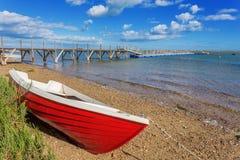 Barco de pesca rojo en la orilla Fotos de archivo