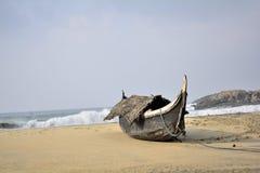 Barco de pesca solitario en una playa imagenes de archivo