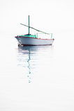 Barco de pesca solo en el mar muy tranquilo Imagen de archivo