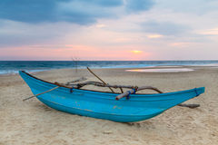 Barco de pesca srilanqués tradicional en la playa arenosa en la puesta del sol. Fotografía de archivo
