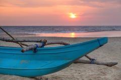 Barco de pesca srilanqués tradicional en la playa arenosa en la puesta del sol. Foto de archivo libre de regalías