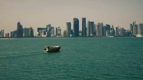 Barco de pesca tradicional que pasa cerca de rascacielos en Doha Qatar Oriente Medio almacen de video