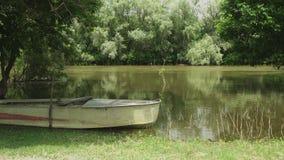 Barco de pesca velho na costa do rio calmo video estoque