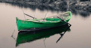 Barco de pesca verde viejo en fondo blanco y negro Imagen de archivo libre de regalías
