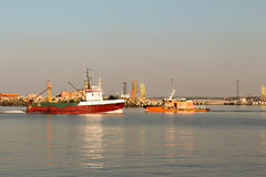 Barco de pesca vermelho que entra no porto de Ventspils Foto de Stock