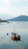 Barco de pesca vermelho vertical no lago calmo Fotografia de Stock