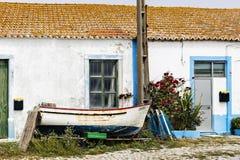Barco de pesca viejo delante de una casa portuguesa Imágenes de archivo libres de regalías