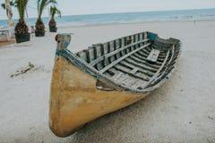 Barco de pesca viejo en la arena con el cielo azul y agua Fotos de archivo libres de regalías