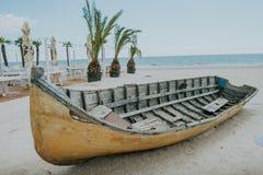 Barco de pesca viejo en la arena con el cielo azul y agua Imagen de archivo