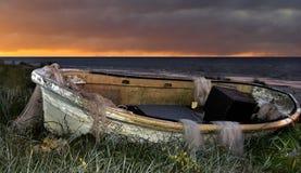 Barco de pesca viejo en la salida del sol foto de archivo